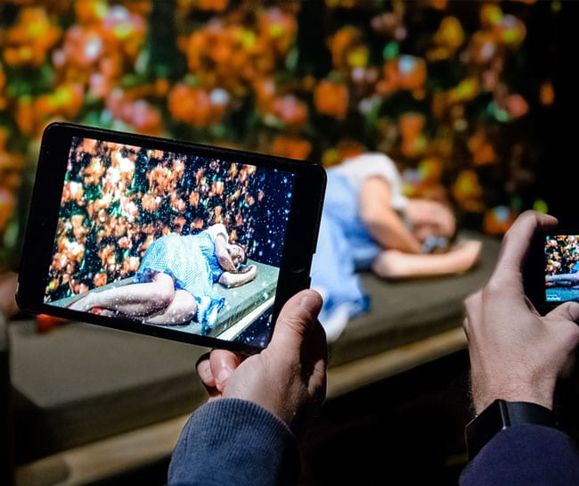 A woman sleeps in a bed of flowers, two handheld devices are filming