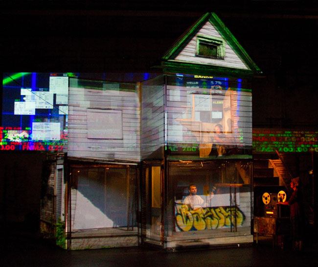 Image of a house on stage with performers and projections